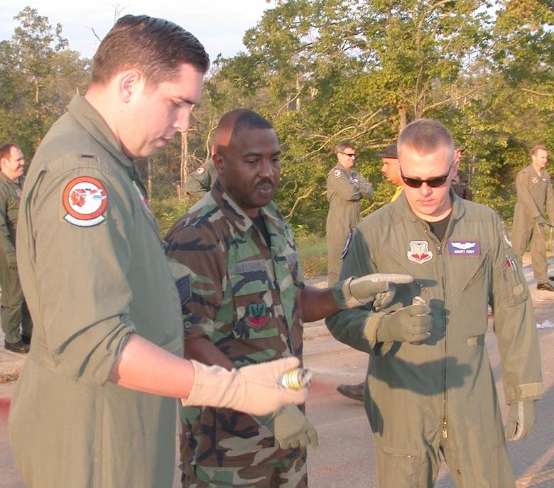 Photo of Airmen looking down at smoke bombs.
