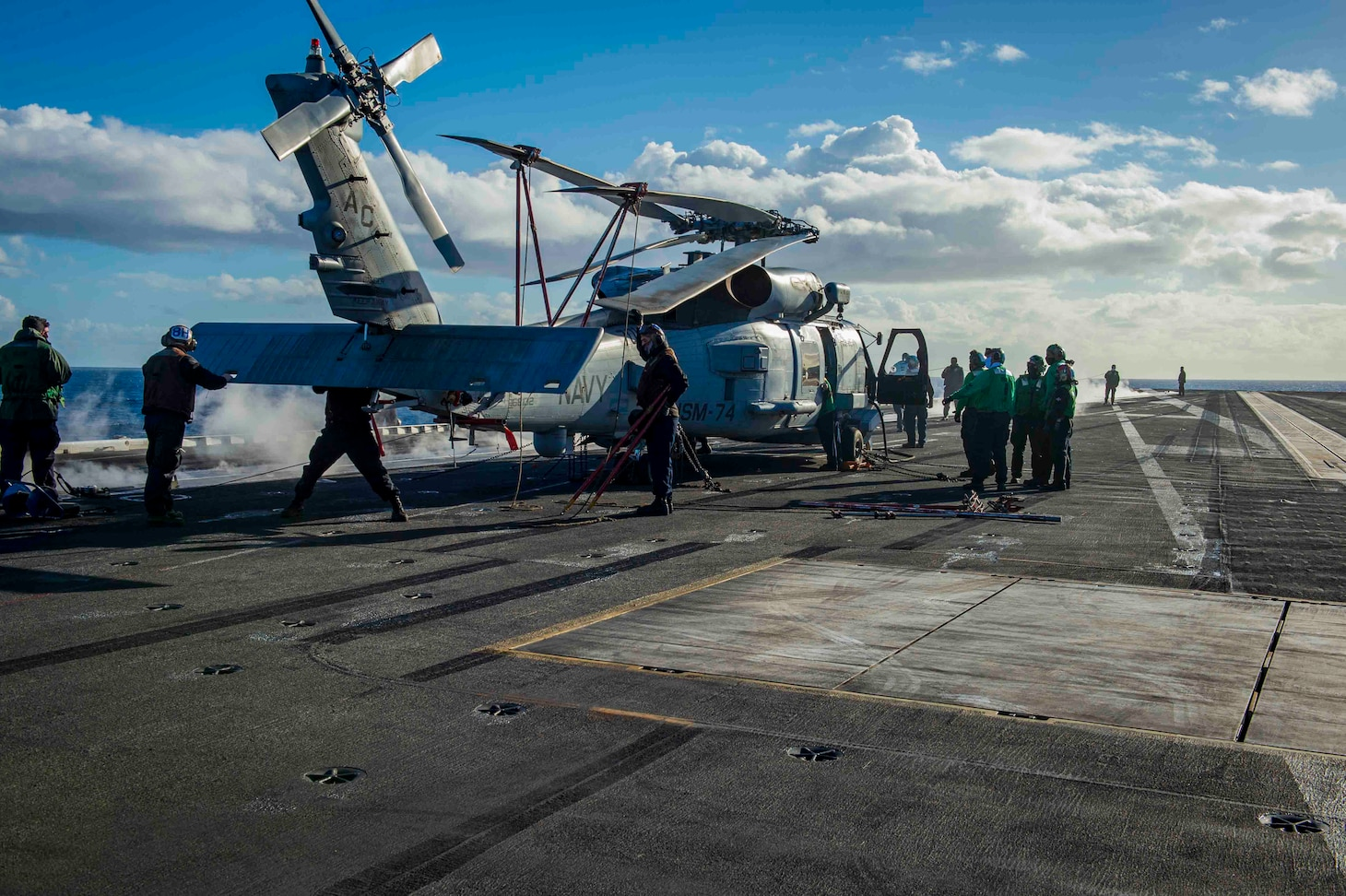 """210228-N-OB471-1071 ATLANTIC OCEAN (Feb. 28, 2021) Sailors perform maintenance on an MH-60R Sea Hawk, attached to the """"Swamp Foxes"""" of Helicopter Maritime Strike Squadron (HSM) 74, aboard the Nimitz-class aircraft carrier USS Dwight D. Eisenhower (CVN 69), in the Atlantic Ocean, February 28, 2021. Ike is on a routine deployment supporting U.S. national security interests in Europe and increasing theater cooperation and forward naval presence in the U.S. 6th fleet area of operations. (U.S. Navy photo by Mass Communication Specialist Seaman Jacob Hilgendorf/Released)"""