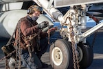 210228-N-OB471-1005 ATLANTIC OCEAN (Feb. 28, 2021) Aviation Machinist's Mate Airman Brandon Luna, from Miami, breaks down chains for an F/A-18E Super Hornet, attached to the
