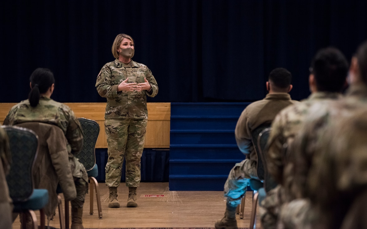 Woman in uniform talks on stage in front of military members