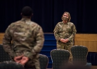 Man in uniform stands up to ask a question to woman in uniform.