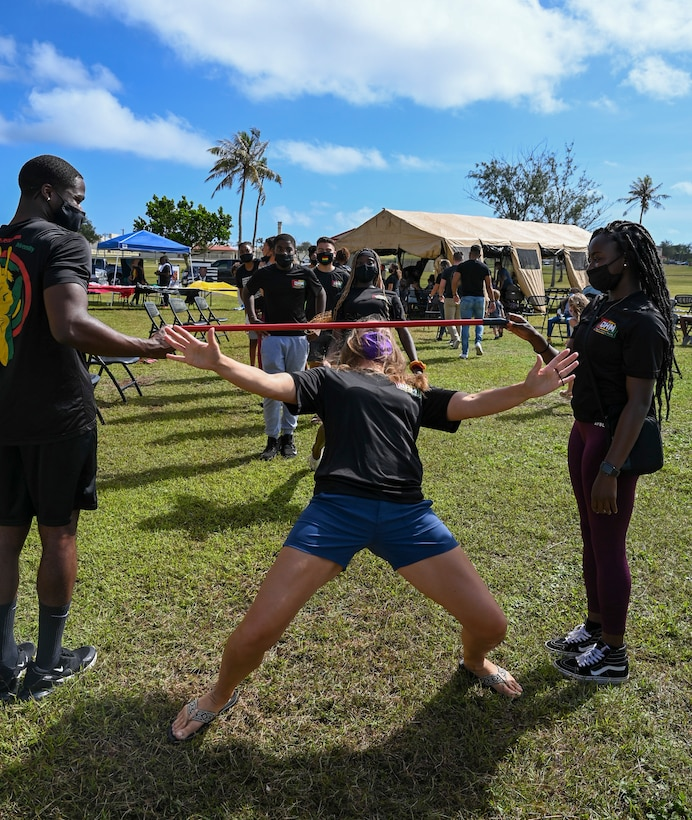"""Guests participate in a limbo challenge during a Black History Month unity event at Andersen Air Force Base, Guam, Feb. 27, 2021. The event focused on this year's message """"The black family: Representation, Identity, And Diversity"""". Guests heard stories from volunteers, participated in a unity walk and played games aimed at bringing service members and families together to remember, recognize, and celebrate Black History Month."""