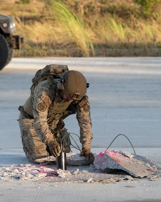 A U.S. Air Force Explosive Ordnance technician plants an explosive during a Rapid Airfield Damage Repair (RADR) Exercise at Andersen Air Force Base, Feb. 12, 2021.
