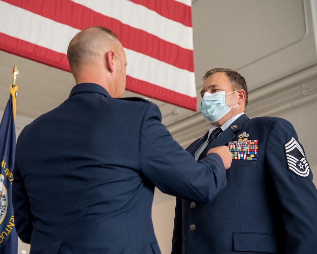 Chief Master Sgt. Robert Crump (right), outgoing equipment maintenance superintendent for the 123rd Maintenance Group, is pinned with the Meritorious Service Medal by Lt. Col. James Embry, commander of the 123rd Maintenance Group, during Crump's retirement ceremony at the Kentucky Air National Guard Base in Louisville, Ky., Sept. 13, 2020. Crump is retiring after more than 39 years of service to the Kentucky Air National Guard. (U.S. Air National Guard photo by Staff Sgt. Joshua Horton)