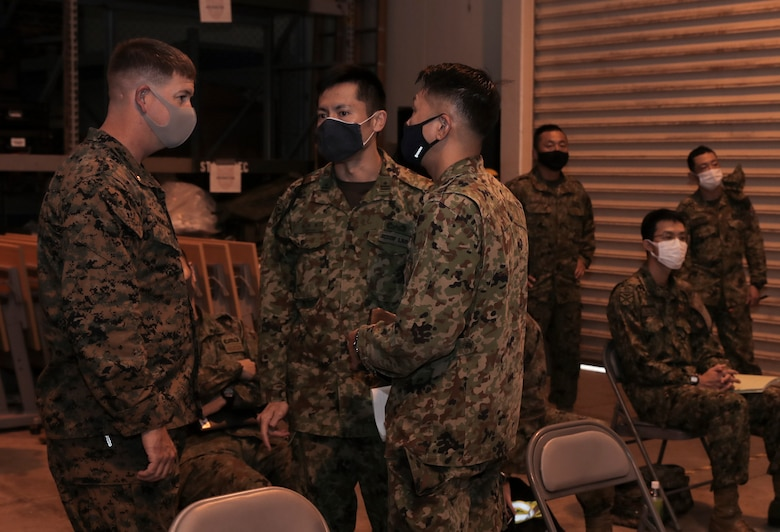 A U.S. Marine with 3rd Marine Expeditionary Brigade and members of the Amphibious Rapid Deployment Brigade of the Japan Ground Self-Defense Force talk before a rehearsal of concept drill for Exercise Yama Sakura 79 at Camp Courtney, Okinawa, Japan, Dec. 5, 2020.