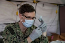 沖縄米海軍病院の衛生下士官が医療従事者に接種する新型コロナワクチン、モデルナを準備する