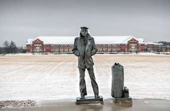 The statue of the Lone Sailor stands on the snow-covered grounds of Recruit Training Command.