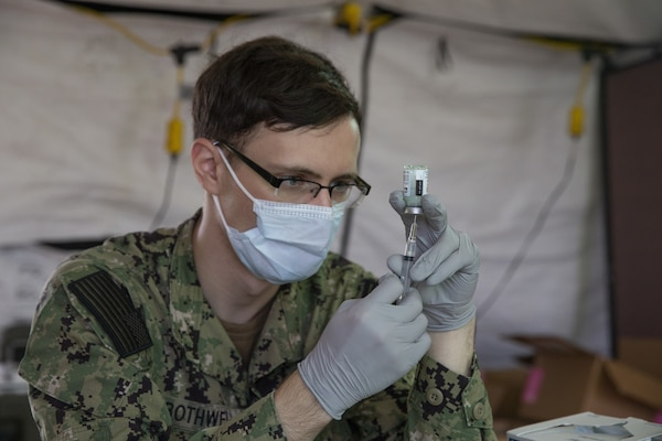 Seaman Dillon Botwell, a hospital corpsman with U.S. Naval Hospital Okinawa, prepares the Moderna COVID-19 vaccine to be administered to U.S. Marine Corps and Navy medical personnel and first responders at the U.S. Naval Hospital Okinawa on Camp Foster, Okinawa, Japan, Dec. 29, 2020.