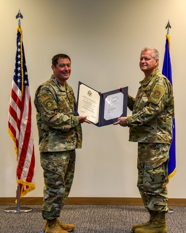 Capt. Anthony Gehl of the 403rd Aircraft Maintenance Squadron, presents Master Sgt. James Rials with his certificate of retirement at the Roberts Consolidated Maintenance Facility Dec. 6, 2020. Rials retired after serving nearly 40 years, all with the Air Force Reserve's 403rd Wing at Keesler Air Force Base (Courtesy photo).