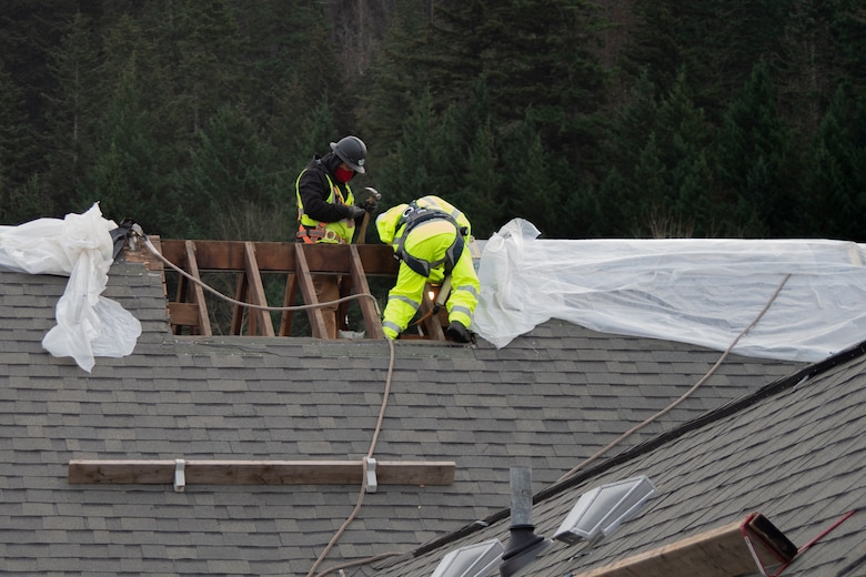Workers remove the rain covering and prepare the Auditorium's roof before the crane lifts the cupola into place.