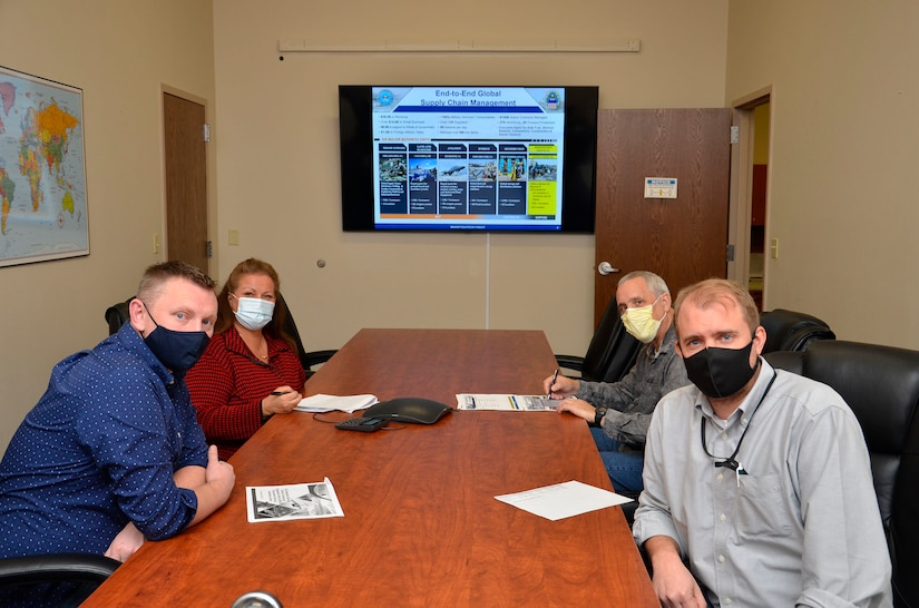 Four people sit around a conference tale looking towards the camera. Each person is wearing a mask.