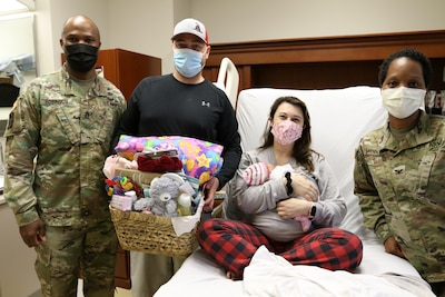Winn Army Community Hospital on Fort Stewart welcomes the first baby delivered at the hospital for 2021. Payton Grace Cowan was born, 6 pounds, 6 ounces, fifty-seven minutes into the New Year to  Capt. Danielle Cowan and her husband Maj. Ryan Cowan.  Maj. Cowan attends the Command and General Staff College and Capt. Cowan is with Fort Stewart's Office of the Staff Judge Advocate. On-hand to greet Payton Grace Cowan and Family were Winn ACH Senior Enlisted Leader, Command Sgt. Maj. Charles Robinson (Left) and Col. Nia Middleton, Deputy Commander for Clinical Services (Right), who presented the Family with best wishes and a gift basket.