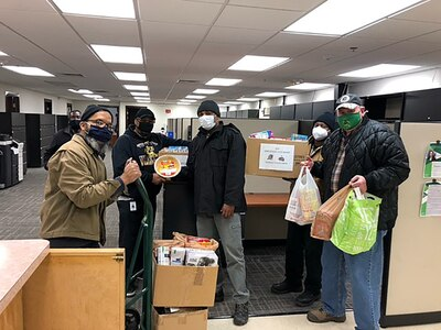 Masked men stand in an office space with boxes and bags of food items for donation.