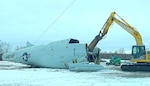 A large shearer tears apart a giant airframe in the snow.