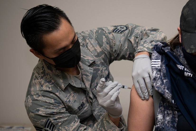 An airman administers a vaccine to another airman.