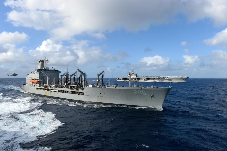 The aircraft carrier USS Theodore Roosevelt (CVN 71), back, transits alongside the Military Sealift Command fleet replenishment oiler USNS Guadalupe (T-AO 200) Jan. 1, 2021.