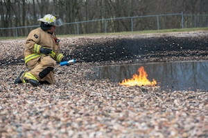Firefighter igniting controlled burn.