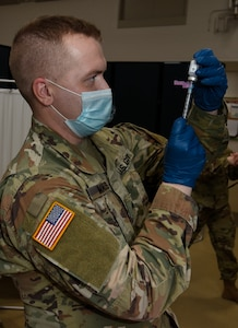 Sgt. Stephen Maynus prepares a dose of COVID-19 vaccine for delivery during a vaccine deployment at Camp Johnson, Vermont, Jan. 4, 2021. Thirty Soldiers and Airmen received vaccinations Jan. 4, with more shots scheduled for Jan. 6 and Jan. 8. Maynus is a health care clinic NCO with the Vermont Army National Guard Medical Detachment.