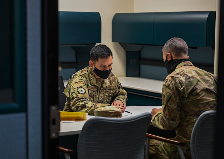 2 uniformed members sit together to do paperwork