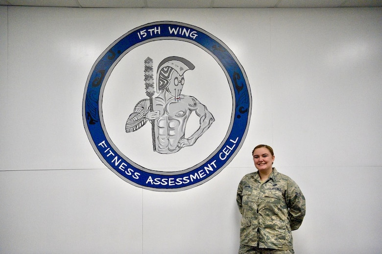 Airman 1st Class Tessa Hanson, 647th Force Support Squadron services journeyman, presents her finished painting project at the Fitness Assessment Cell at Joint Base Pearl Harbor-Hickam, Hawaii, Dec. 12, 2020. Hanson completed a series of paintings at the FAC with the purpose of motivating Airmen testing during their physical fitness assessment. (Air Force photo by 2nd Lt Benjamin Aronson)