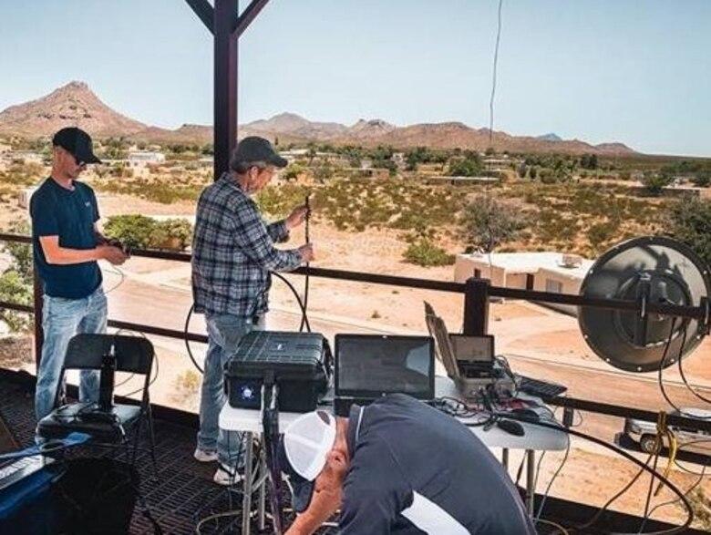 three men setting up equipment in the desert