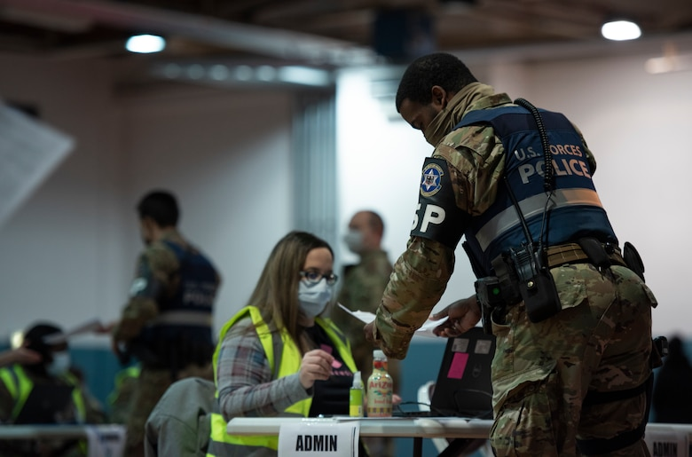 A 569th U.S. Forces Police Squadron first responder hands a document to an administrator at a vaccine clinic on Ramstein Air Base, Germany, Jan. 4, 2021.