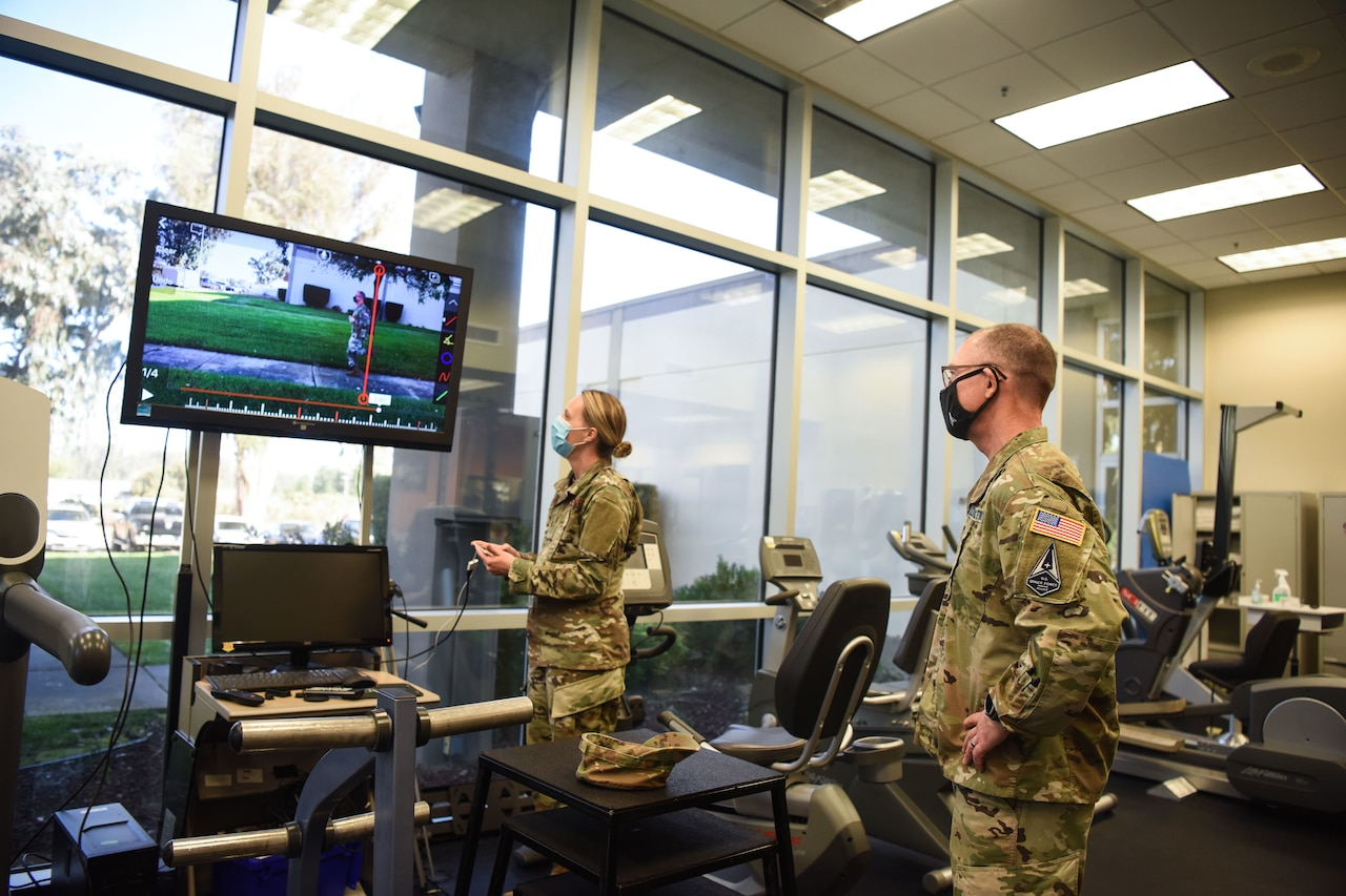 An airman briefs another airman while viewing a computer screen.