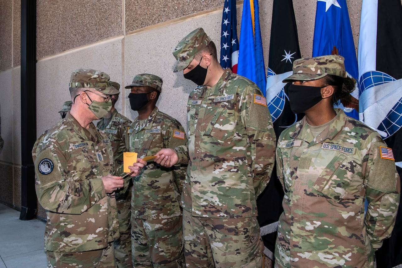 Man in a military uniform hands service identification tapes to new Space Force guardians.