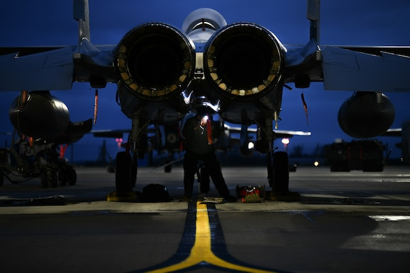 Staff Sgt. Brandon Thomas-Volkov, 494th Aircraft Maintenance Unit dedicated crew chief, inspects the underside of an F-15E Strike Eagle before the first takeoffs of the new year at Royal Air Force Lakenheath, England, Jan. 5, 2021. Dedicated Crew Chiefs are responsible for managing and supervising all maintenance on their respective aircraft by coordinating with other maintenance specialties such as propulsion, hydraulics and fuels to ensure the aircraft is operational in a timely manner. (U.S. Air Force photo by Senior Airman Madeline Herzog)