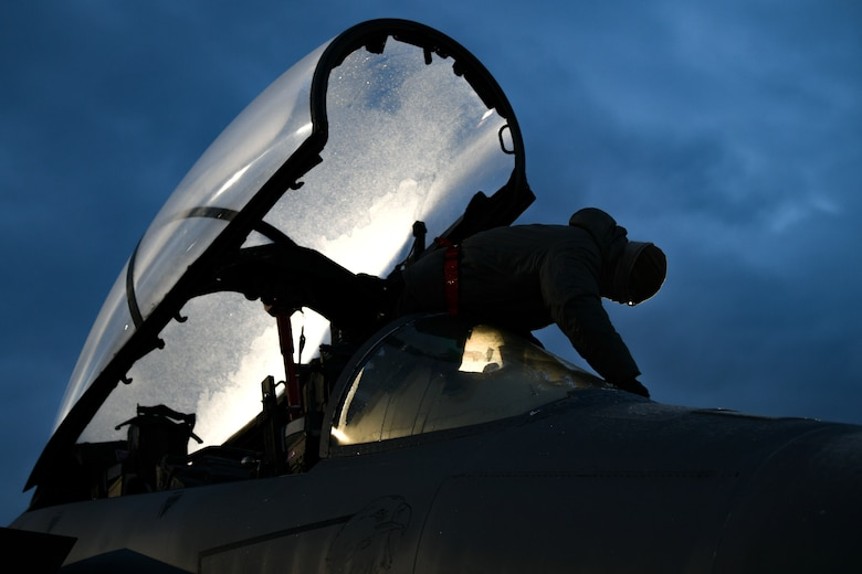 Airman 1st Class Matthew Perkins, 494th Aircraft Maintenance Unit assistant dedicated crew chief, scrapes the frost off of the canopy of an f-15E Strike Eagle before the first takeoffs of the new year at Royal Air Force Lakenheath, England, Jan. 5, 2021. ADCCs are responsible for supporting dedicated crew chiefs with all work pertaining to their aircraft. (U.S. Air Force photo by Senior Airman Madeline Herzog)