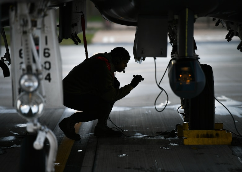 Staff Sgt. Virgil Lawson Jr., 494th Aircraft Maintenance Unit dedicated crew chief, inspects the wheels of an F-15E Strike Eagle before the first takeoffs of the new year at Royal Air Force Lakenheath, England, Jan. 5, 2021. Dedicated Crew Chiefs are responsible for managing and supervising all maintenance on their respective aircraft by coordinating with other maintenance specialties such as propulsion, hydraulics and fuels to ensure the aircraft is operational in a timely manner. (U.S. Air Force photo by Senior Airman Madeline Herzog)