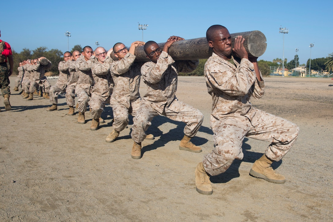 Marine Corps recruits perform squats in a line while carrying a log.