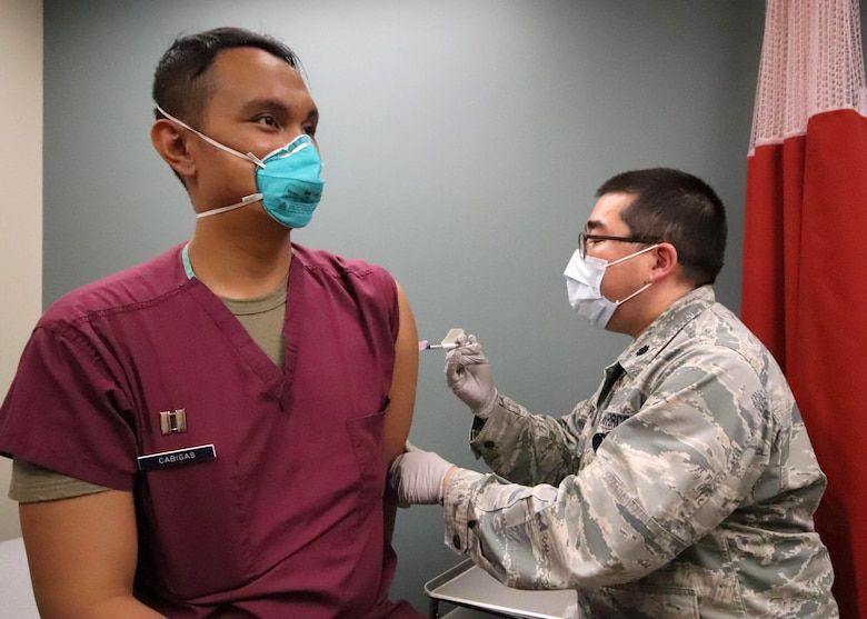 U.S. Air Force Lt. Col. Edward Champoux, the 673d Health Care Operations Squadron Allergy and Immunization Clinic chief and Pacific Air Forces regional allergist, administers the first of a two-dose series of a COVID-19 vaccine to U.S. Air Force Capt. Orlando Cabigas, a clinical nurse with the 673d Health Care Operations Squadron Emergency Services Flight, at Joint Base Elmendorf-Richardson, Alaska, Dec. 30, 2020. Upon receiving the initial shipment of the vaccine, JBER began inoculating personnel following the Centers for Disease Control and Prevention's prioritization guidelines. The vaccine is part of Operation Warp Speed, a national initiative to accelerate the development, production and distribution of safe and effective COVID-19 vaccines, therapeutics and diagnostics.