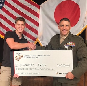 Lt. Col. Christopher Tsirlis presents his son, Christian, with the $180,000 Naval Reserve Officer Training Corps scholarship during his high school awards night in 2019. Christian earned the scholarship in 2019 after a rigorous and competitive application process. He proved he was worthy of the scholarship through his academic achievements and proven leadership abilities as the captain of his school football and track teams. He also demonstrated outstanding physical fitness abilities.