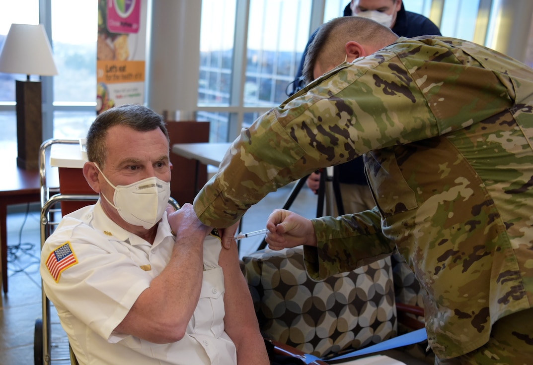 Man gets vaccination from a man in military uniform