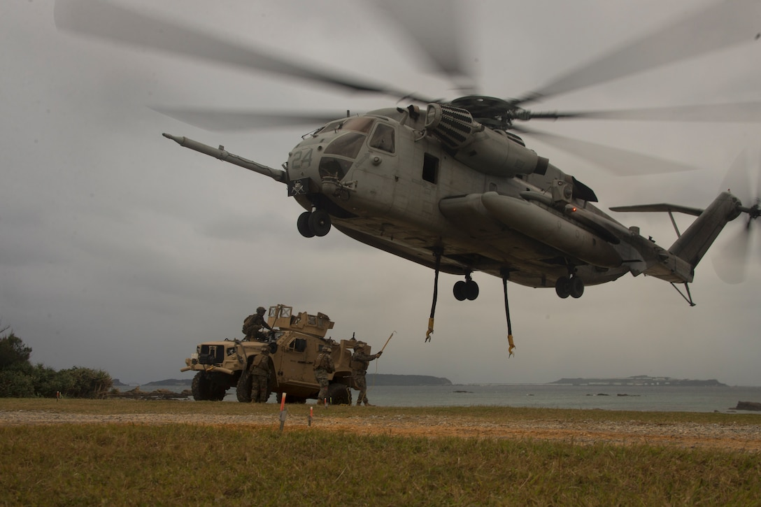 Marines prepare to attach a vehicle to an aircraft in a field.