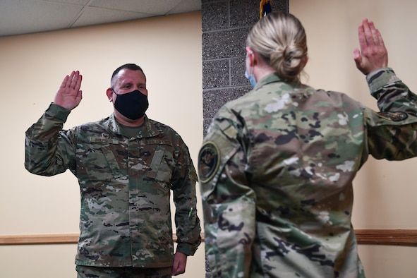Col. Richard Bourquin (left), Space Delta 4 commander, is commissioned into the U.S. Space Force by 1st Lt. Sydney Hauver (right), 11th Space Warning Squadron executive officer,  during a small ceremony at Buckley Air Force Base, Colo., Jan. 5, 2021.