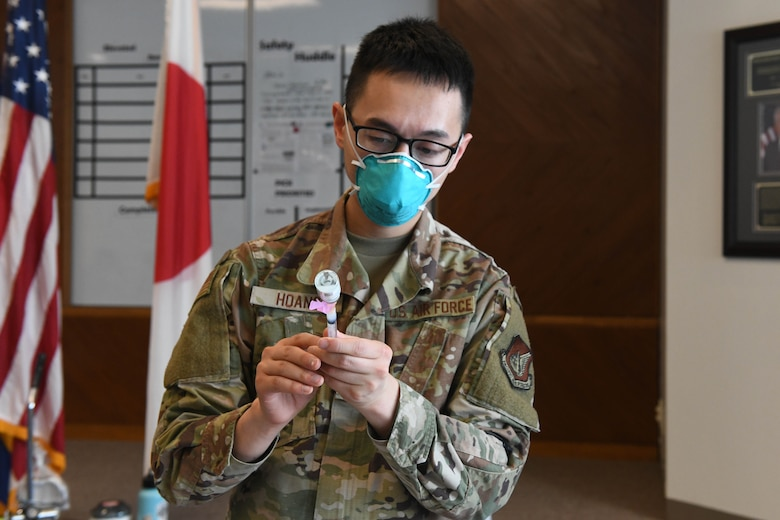 U.S. Air Force Tech. Sgt. David Hoang, an allergy and immunizations technician with the 18th Healthcare Operations Squadron, draws the Moderna's vaccine into a syringe at Kadena Air Base, Japan, Dec. 28, 2020. As part of DoD's strategy for prioritizing, distributing and administering the COVID-19 vaccine, those providing direct medical care and emergency services will be prioritized to receive the vaccine at units based in Japan, including Kadena AB. (U.S. Air Force photo by Airman 1st Class Yosselin Perla)