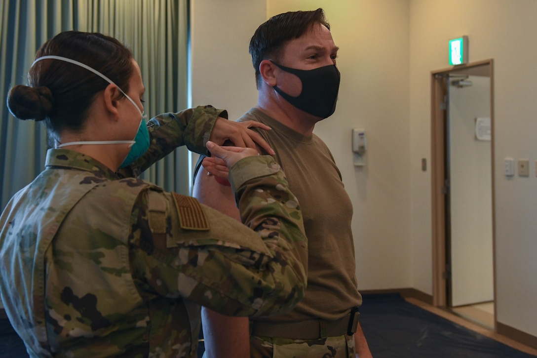 U.S. Air Force Tech. Sgt. Christina Reynoso, the NCO in charge of the immunizations clinic with the 18th Healthcare Operations Squadron, administers the Moderna's vaccine to Col. Jay Veeder, commander of the 18th Medical Group at Kadena Air Base, Japan, Dec. 28, 2020. As part of DoD's strategy for prioritizing, distributing and administering the COVID-19 vaccine, those providing direct medical care and emergency services will be prioritized to receive the vaccine at units based in Japan, including Kadena AB. (U.S. Air Force photo by Airman 1st Class Yosselin Perla)