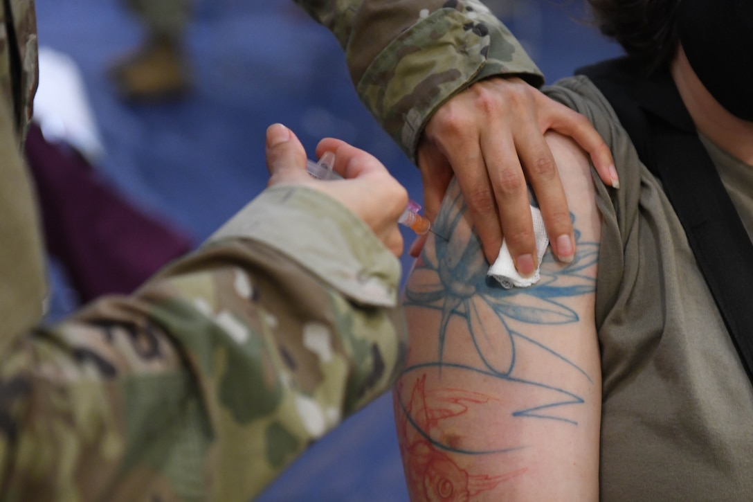 U.S. Air Force Tech. Sgt. Christina Reynoso, the NCO in charge of the immunizations clinic with the 18th Healthcare Operations Squadron, administers the Moderna's vaccine to U.S. Air Force Capt. Deanna Haxton, a clinical nurse with the 18th HCOS at Kadena Air Base, Japan, Dec. 28, 2020. As part of DoD's strategy for prioritizing, distributing and administering the COVID-19 vaccine, those providing direct medical care and emergency services will be prioritized to receive the vaccine at units based in Japan, including Kadena AB. (U.S. Air Force photo by Airman 1st Class Yosselin Perla)