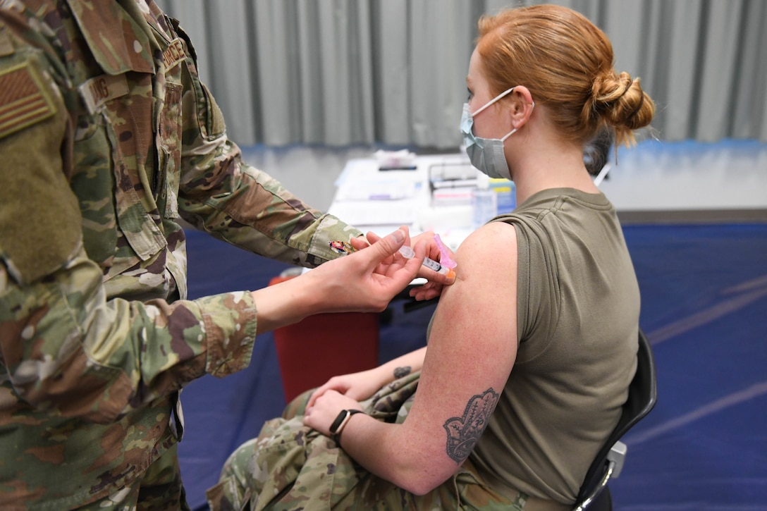 U.S. Air Force Tech. Sgt. David Hoang, an allergy and immunizations technician with the 18th Healthcare Operations Squadron, administers the Moderna's vaccine to Senior Airman Julia Rodriguez, a laboratory technician with the 18th Medical Support Squadron at Kadena Air Base, Japan, Dec. 28, 2020. As part of DoD's strategy for prioritizing, distributing and administering the COVID-19 vaccine, those providing direct medical care and emergency services will be prioritized to receive the vaccine at units based in Japan, including Kadena AB. (U.S. Air Force photo by Airman 1st Class Yosselin Perla)