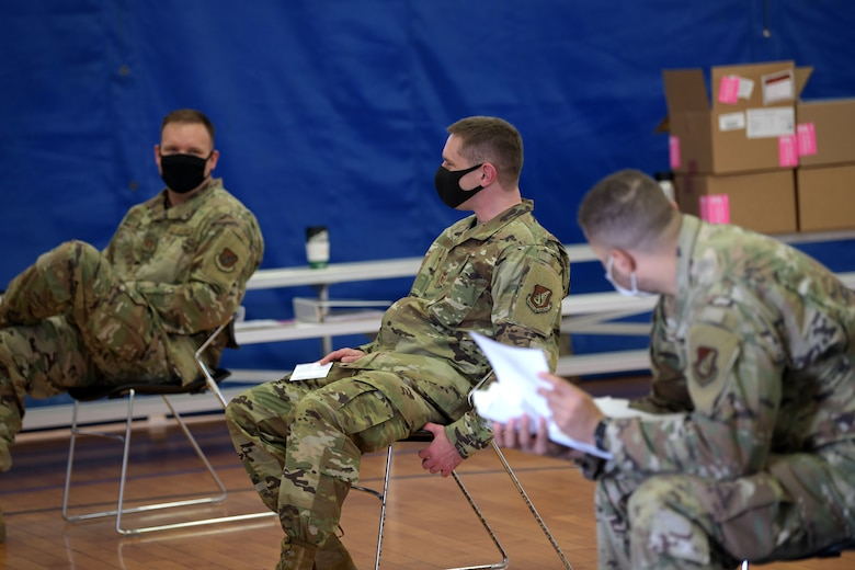 U.S. Air Force Capt. Joshua Craig (left), Tech. Sgt. Nathan Wehrle (middle) and Staff Sgt. Bryan Cooper (right) from the 18th Aeromedical Evacuation Squadron sit patiently waiting through the observation period after receiving the Moderna COVID-19 Vaccine, Jan. 4, 2021, at Kadena Air Base, Japan. As part of the DoD strategy for prioritizing, distributing and administering the COVID-19 vaccine, those providing direct medical care and emergency services will be prioritized to receive the vaccine at units based in Japan, including Kadena AB. (U.S. Air Force photo by Airman 1st Class Rebeckah Medeiros)