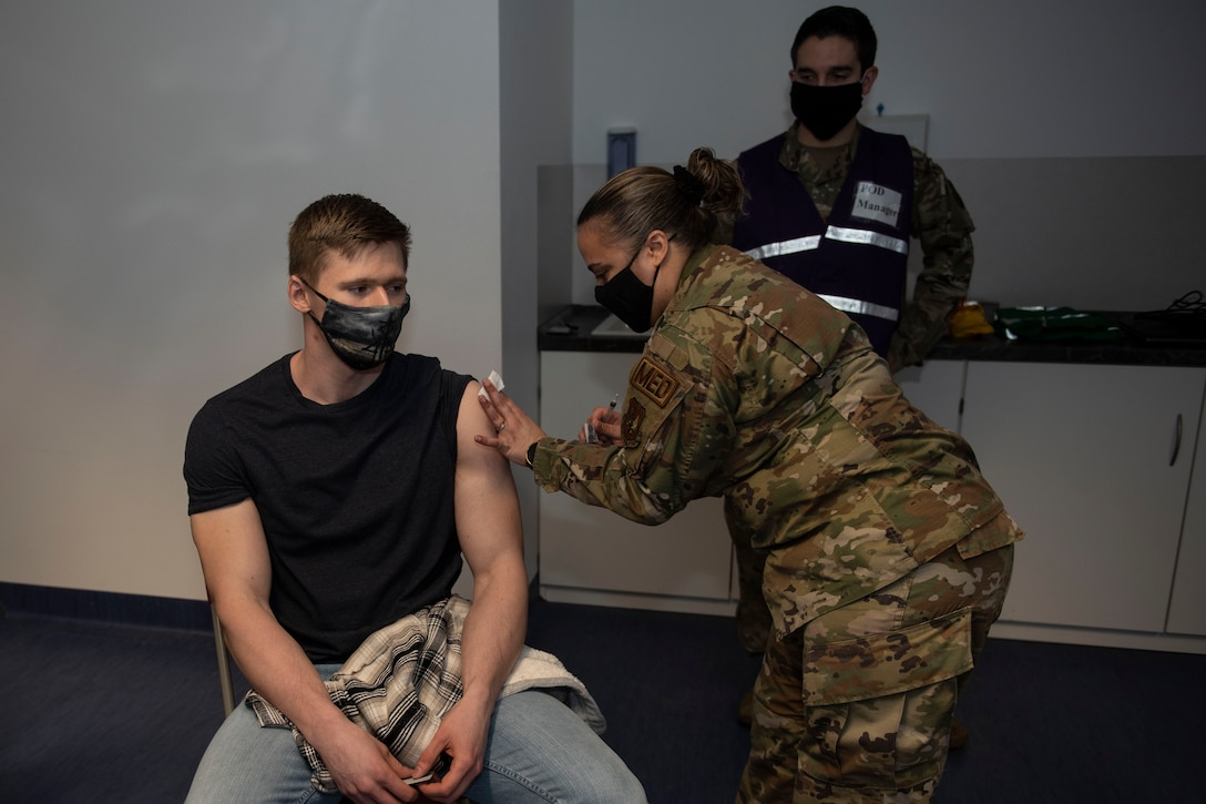 U.S. Air Force Senior Airman Brandon Franklin, 52nd Civil Engineer Squadron Fire and Emergency Services firefighter, receives the COVID-19 vaccine from Tech Sgt. Valeria Feist, 52nd Medical Operations Squadron allergy and immunization technician, Jan. 4, 2021, at Spangdahlem Air Base, Germany. Capt. Matthew Jordan, 52nd Medical Support Squadron chief of pharmacy operations, back, oversaw and hosted the first distribution of COVID-19 vaccinations for 52nd Fighter Wing Airmen, and ensured the process and comfort of service members were a priority. (U.S Air Force photo by Senior Airman Melody W. Howley)