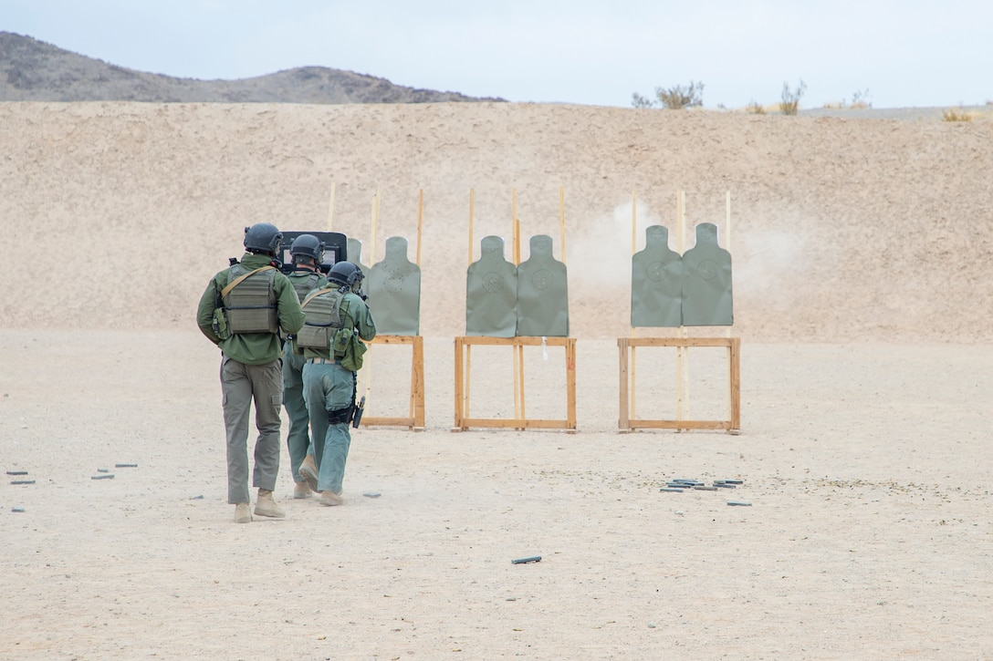 U.S. Marine Corps Sgt. Marcus Edwards, team commander, Special Reaction Team, Provost Marshall's Office, Marine Air Ground Task Force Training Command, coaches his Marines on movement and breaching techniques during an SRT familiarization range at Marine Corps Air Ground Combat Center, Twentynine Palms, California, Dec. 11, 2020. SRT Marines are military police officers trained in hostage situation, active shooter and barricaded suspect response. (U.S. Marine Corps photo by Lance Cpl. Joshua Sechser)