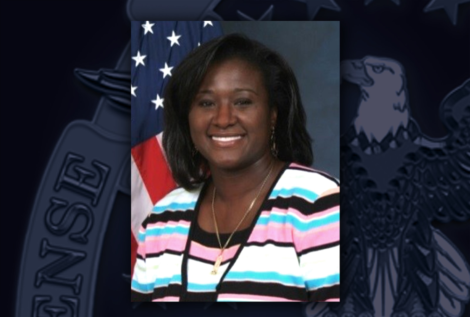Head and shoulders image of a black woman wearing a black, white, pink and blue striped sweater posing in front of the US flag.