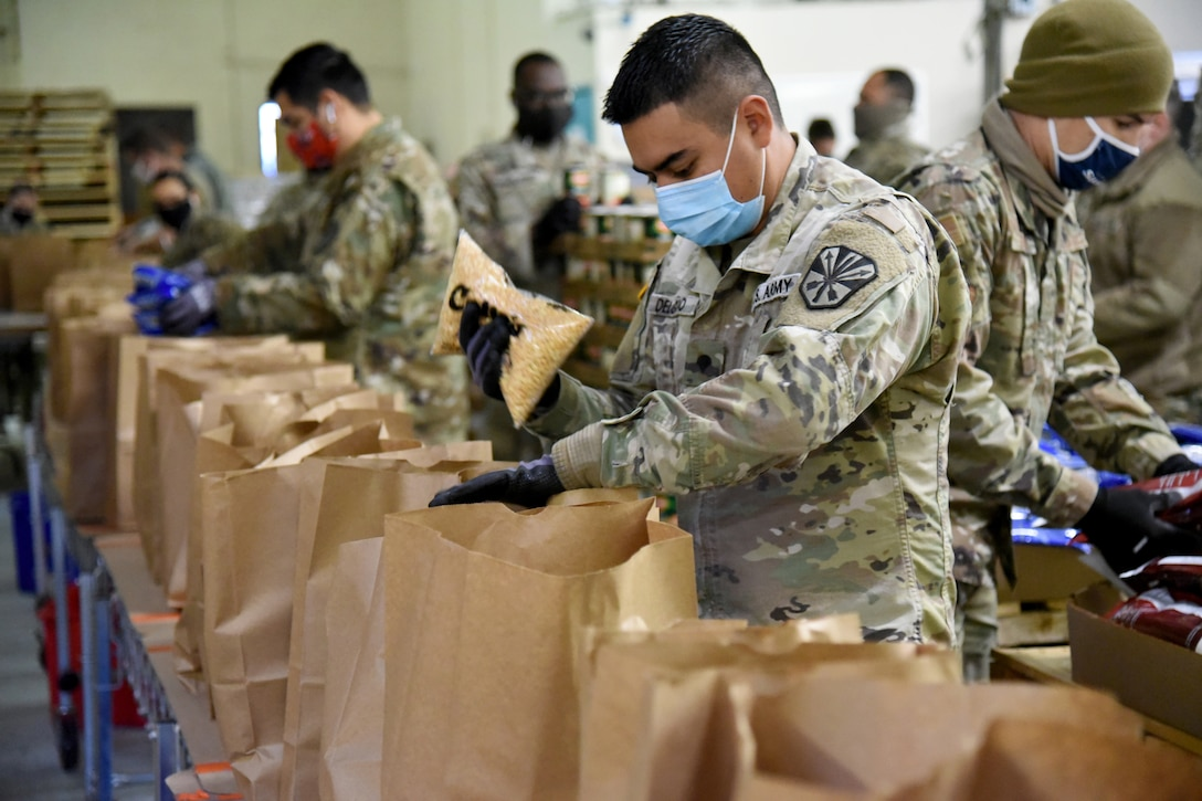Service members fill paper bags with groceries.