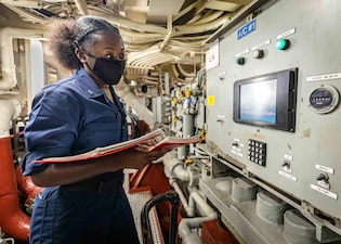 Machinist Mate 3rd Class Jasmine Booker stands watch aboard USS John S. McCain (DDG 56).
