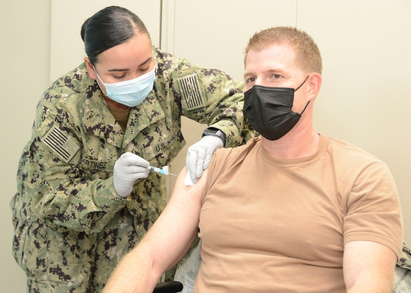 MANAMA, Bahrain (December 30, 2020) Capt. Greg Smith, Naval Support Activity (NSA) Bahrain's commanding officer, receives the COVID-19 vaccine from Hospital Corpsman 2nd Class Rose Martinez. The vaccine is being administered in phases based on priority levels to reduce the burden of COVID-19 in high-risk populations and simultaneously mitigate risk to military operations. (U.S. Navy photo by Mass Communication Specialist 1st Class Justin Yarborough/Released)