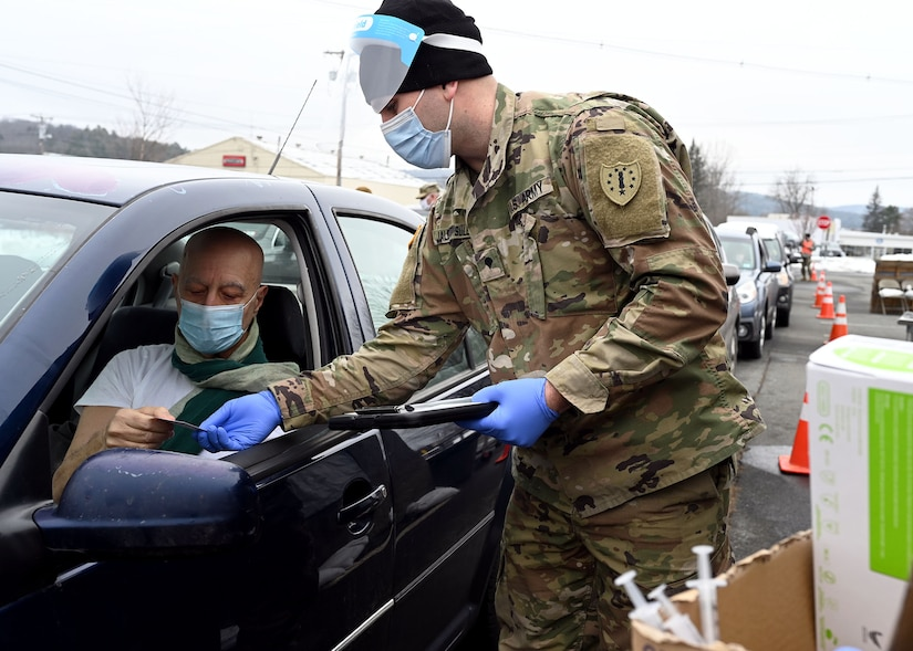 Spc. Blake Jalbert-Sullivan, a combat medic with NHARNG's Medical Detachment, goes over vaccination paperwork with Will Hill, a 70-year-old registered nurse, Jan. 5 in Lebanon.