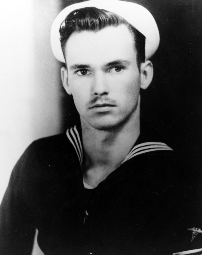 A sailor in uniform looks at the camera.